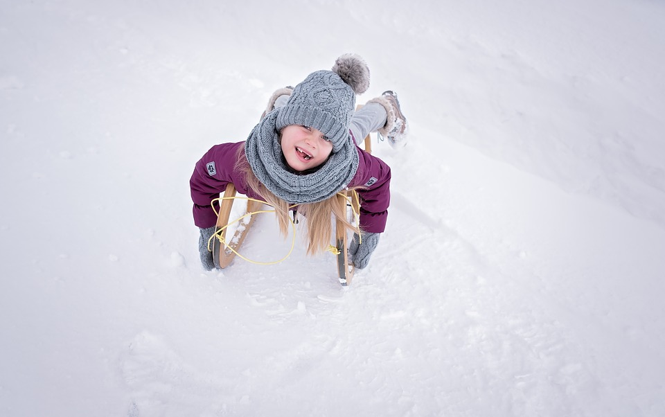 Kind rodelt auf einem Schlitten im Schnee